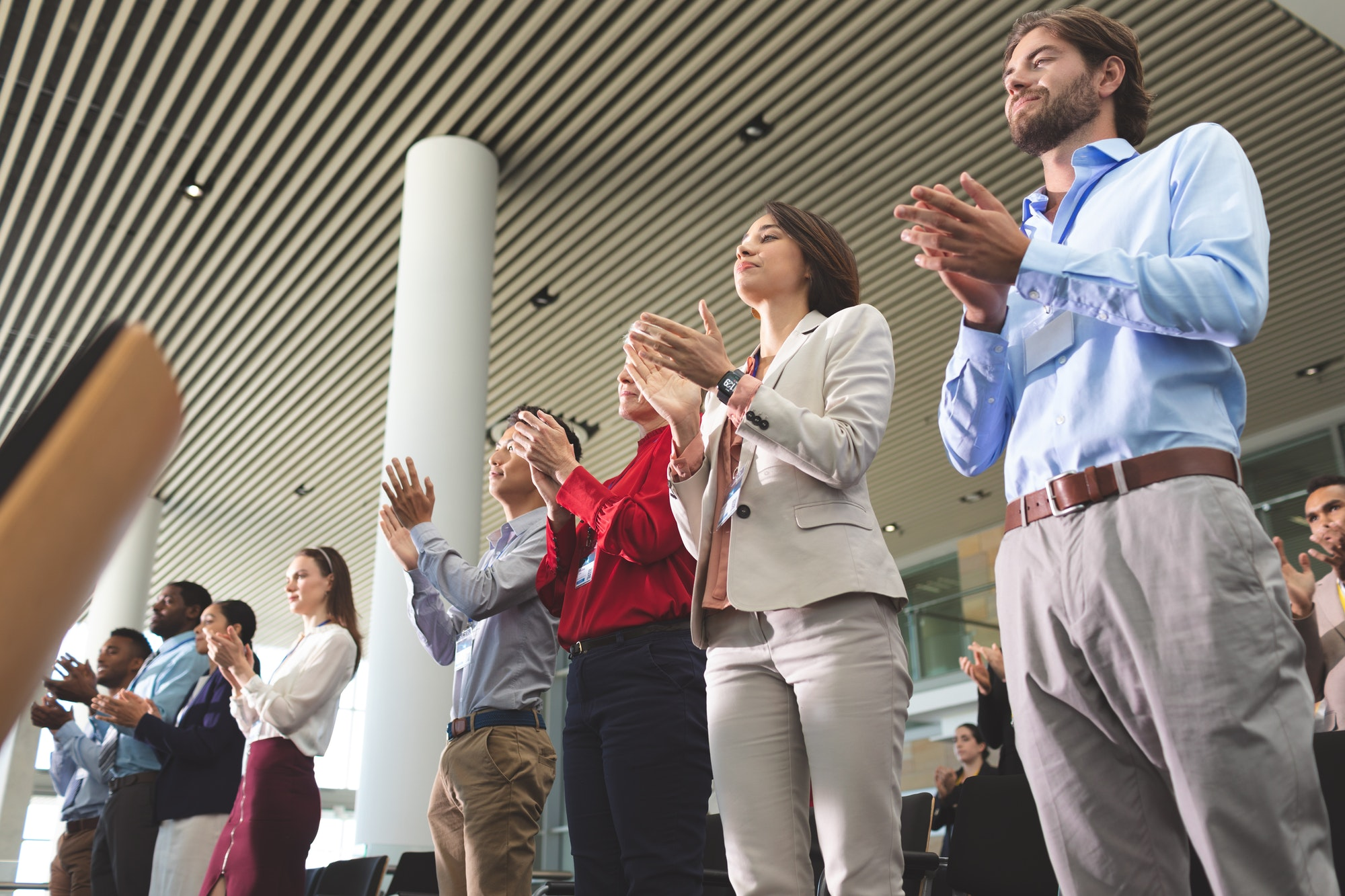Business people clapping while standing at a business seminar in office