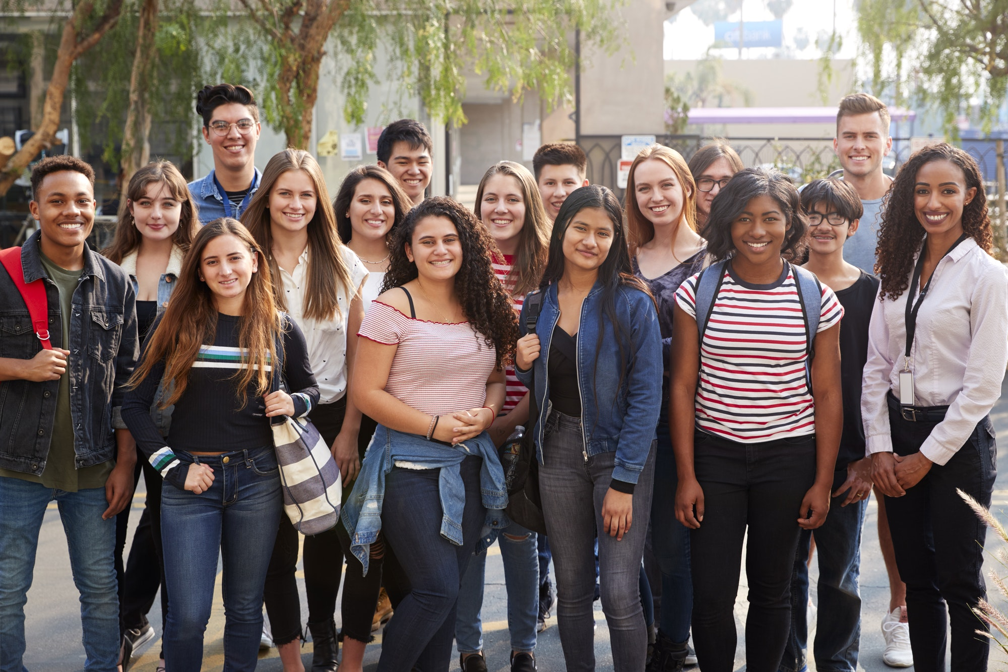 Portrait Of Smiling Male And Female College Students With Teachers Outside School Building